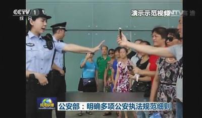 """公安部发布的演示视频中,民警执法时,面对群众围观拍摄,民警要自觉接受监督,习惯在""""镜头""""下执法。央视截屏"""