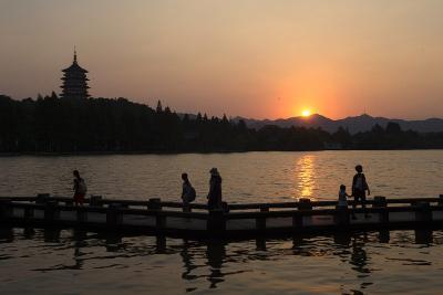 """8月29日,游客在西湖边欣赏""""雷峰夕照""""景观。"""