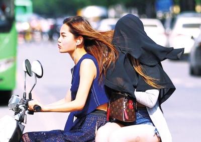 郑州街头市民用衣服蒙头抵挡烈日