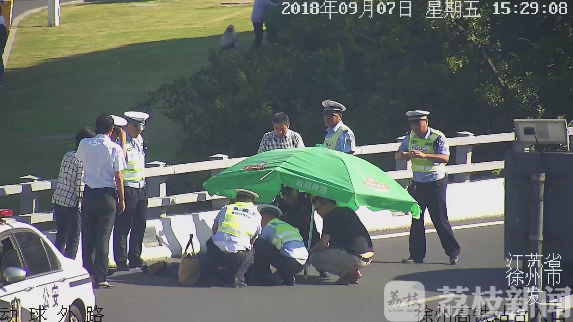 徐州:女子高铁送站平台晕倒 警民联手撑伞营救