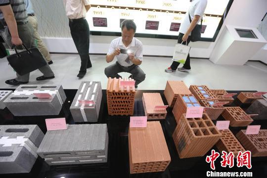 """资料图:节能""""板砖""""亮相南京绿色建筑材料展 ,参观者被展出的""""板砖""""吸引。泱波 摄"""