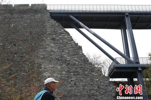 """资料图:南京650岁古城墙""""植入""""了灰色的现代钢结构桥梁。 泱波 摄"""