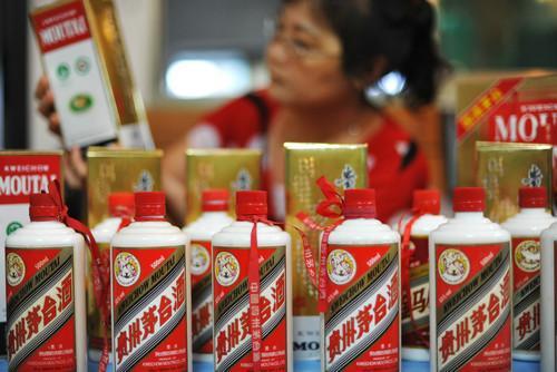 资料图片:2013年8月31日,海南琼海一名顾客在商店选购茅台酒。新华社发