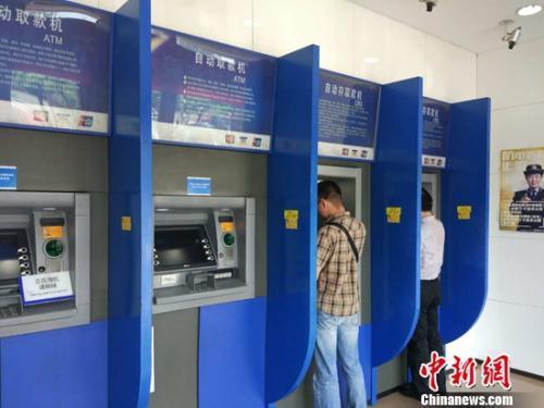 民众在自动取款机上取钱。<a target=&apos;_blank&apos; href=&apos;http://www.chinanews.com/&apos; ></table>中新网</a>记者 李金磊 摄
