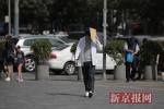 高温暴晒气温升至39°C 北京街头美女花式遮阳
